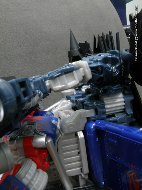 Step 2 - Divide body of JetFire into 2 half horizontally, hook the silver piece of JetFire at the back of Optimus Prime.